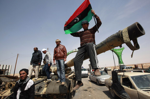 A man holding a Kingdom of Libya flag stands atop a burnt tank on the outskirts of the town of Ajdabiyah